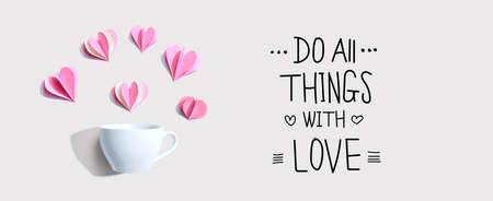 Do all things with love message with a coffee cup and paper hearts - flat lay