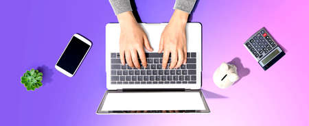 Woman using a laptop computer with a piggy bank 版權商用圖片