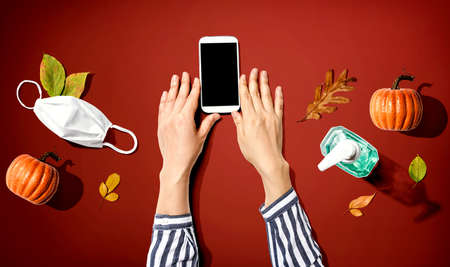 Smartphone with mask and sanitizer bottle in Autumn 版權商用圖片