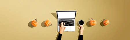 Autumn pumpkins with person using a laptop computer 版權商用圖片