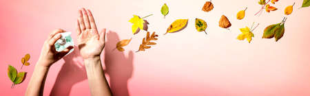 Applying sanitizer gel with autumn leaves