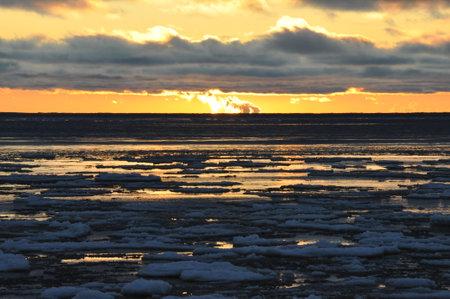 Winter sea promenade at sunset. Ice floes float along the coast, illuminated by the sun. Standard-Bild