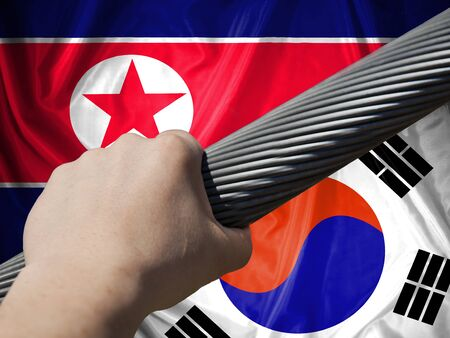 The concept of applying the two countries: North  Korea and South Korea. Flag of  North  Korea, with the flag of South Korea, man's hand compresses stranded steel rope.
