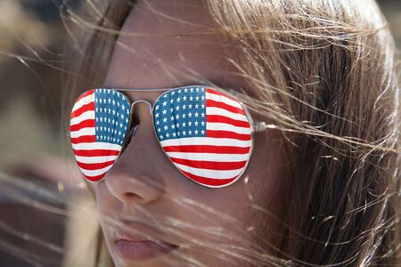 America's Independence Day- 4th of July, the US flag is reflected in the sunglasses of a beautiful American woman