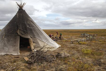 Women of Nenets nationality stay near their yurts and sled. Nomad Nenets people live in yurts whole year, migrate with reindeer herd in tundra around polar circle. Фото со стока