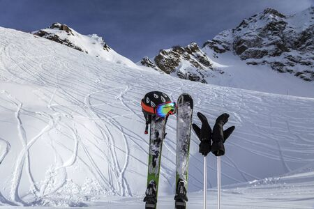 Skiing and ski poles stand vertically in the snow against the background of the ski descent