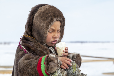 Nadym, Russia - april 27, 2018:tundra, open area, the boy is eating ice cream in cold winter weather, the boy  in national clothes, editorial.