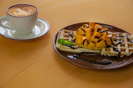 Viennese waffles with ice cream and slices of mango doused with chocolate, on an orange background
