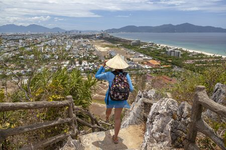 Travel and tourism, a backpacker girl stands on top of the Marble Mountains in Da Nang, Vietnam