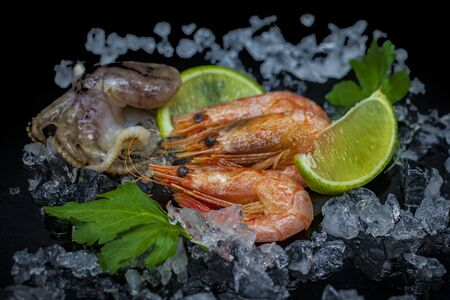 Seafood, octopus and prawns with lime on ice, on a black background