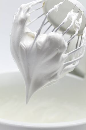 Creamy cream for meringue roll, whipped cream on a whisk of a mixer, close-up Stock Photo