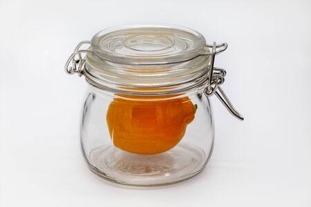 Money saving concept. Meyer, orange, lemon from Uzbekistan, lemon in a glass jar on a white background, isolated