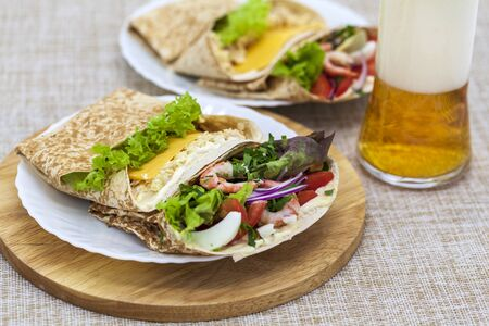 tortillas in envelopes, stuffed with shrimp and vegetables, parmesan and tuna fillet meat, beer snack, fajita wrap sandwich  版權商用圖片