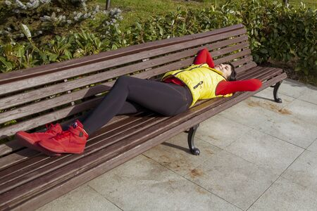 girl in a tracksuit lies on a bench