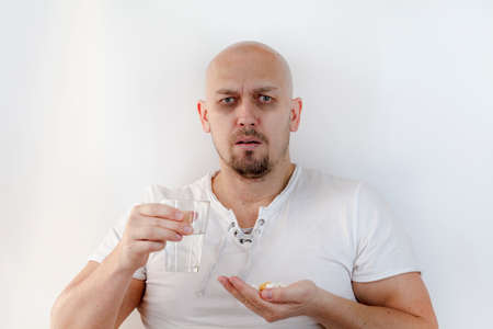 Feeling sick concept. Daily norm of vitamins, effective drugs, modern pharmacy for body and mental health concept . Man with glass of water, takes pills