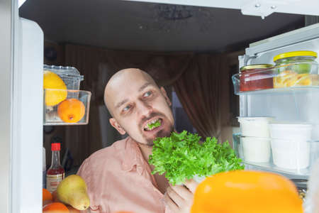 The hungry man. A man looks at the refrigerator at night, a hungry man with a look is ready to eat everything, eats lettuce