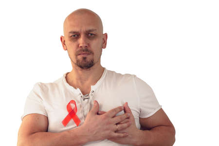 Medicine, cancer, young handsome bald man holding cancer ribbons, standing on an isolated white background with a confident expression, holding  heart with two hands.