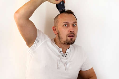 Hair problems, struggle with baldness, a man shaves his head with an electric razor