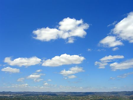 disperse: mountain landscape with several scattered villages with fluffly white clouds and blue sky.