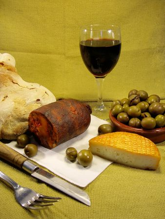 Traditional portuguese lunch meal, including, wine, cheese, chorizo, olives and bread, with a yellow cloth behind.