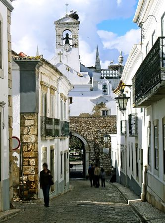 Well known entrance arc with storks on the bell tower, located on Faro, Portugal.
