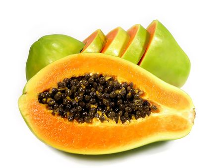One papaya sliced on half, while another behind is cut on horizontal slices, isolated on a white background. Stock Photo