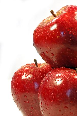 Close up view of three red apples on the right half side of the screen, with drops of water, isolated on a white background.
