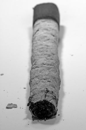 inhaled: Dying out cigar with ash isolated on a white background.