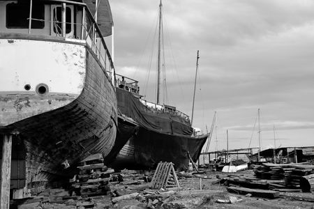 View of an abandoned shipyard with two broken boats on the side. photo