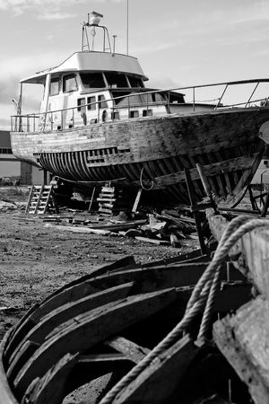 View of an abandoned shipyard with two broken boats . photo