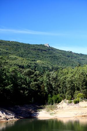 tight filled: View of a forest lake with a rock on top of the hill with blue sky in Sintra, Portugal.