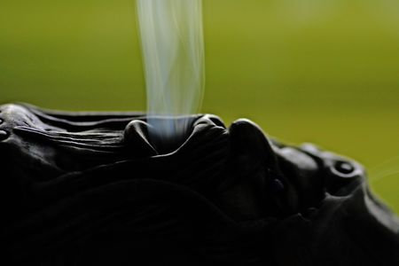 Close view of a smoking doll with smoke getting out of it's mouth. Banco de Imagens