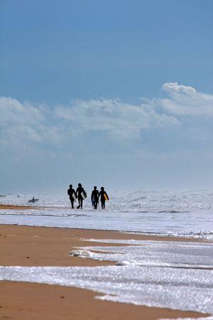 bodyboard: Four bodyboard surfers walking down the shoreline of a beach. Stock Photo