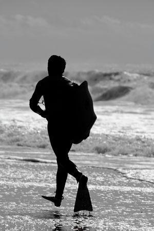 bodyboard: Silhouette of a bodyboard surfer running on the shoreline of a beach.