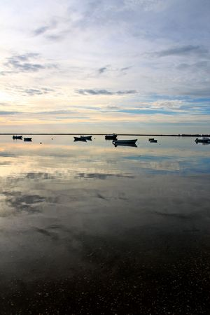 wideview: Wideview of an early morning with lush fluffy cloud sky with several fishing boats and reflection on the water.