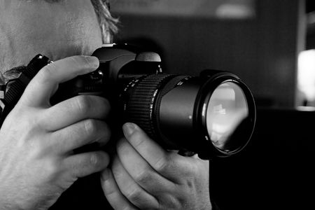 Close up view of a photographer taking a picture with a digital camera.