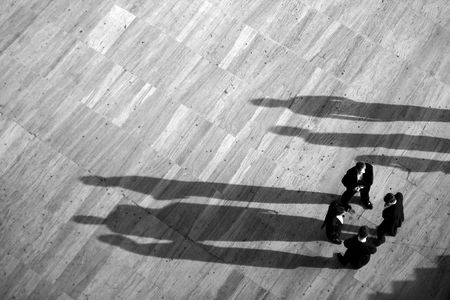 gathering: Group of business men gathered on a circle with long shadows.