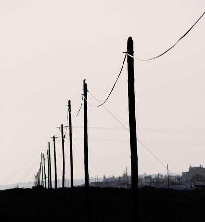 View of some aligned electricity poles in silhouettes at dawn. photo