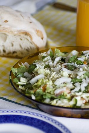 Table with typical portuguese salad with onions, tomatoes and pepper with orange juice and loaf of bread. photo