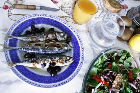 On the table, grilled mackerels poured with olive oil, oranje juice and bread. photo