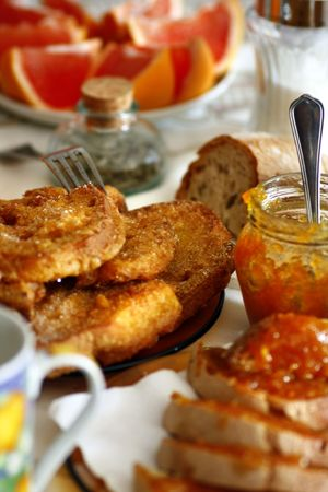 View of a breakfast table with golden slices of bread, orange jam and milk.