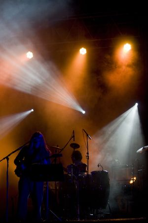 View of two musicians, one on the guitar and another on drums on a concert. Stock Photo