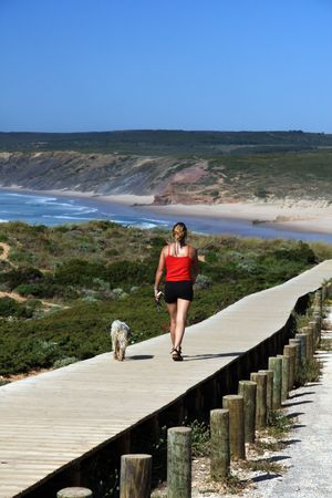Woman walking a borderwalk passage near Carrapateira bay area near SagresPortugal.