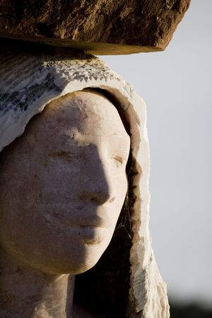 hardworker: Closeup view of a stone statue face of a young woman.