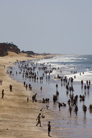 overcrowded: Overcrowded beach shoreline with many silhouettes of people.