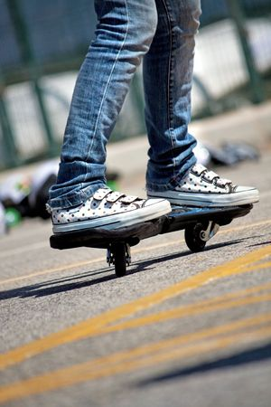 View of the legs of a young street-surfing adept female making some moves. Stock Photo