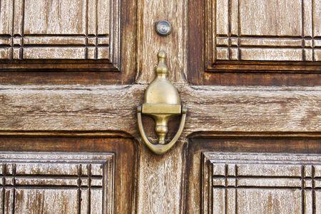 Closeup view of an entrance door wood texture with a golden knob. photo