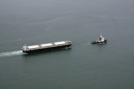 escorted: Aerial view of a cargo transportation ship escorted by a small fishing boat.