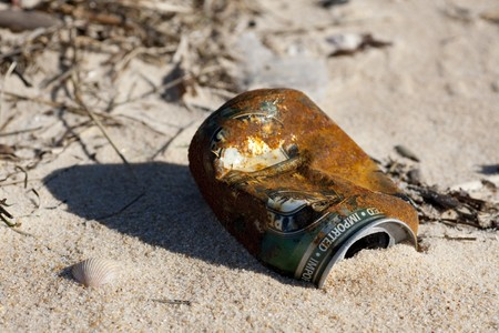 Close view of an abandoned and rusty can of beer on the beach. photo