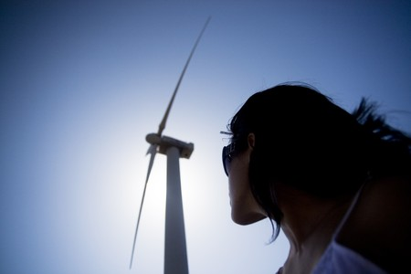 View of a young girl watching a windmill. Stock Photo